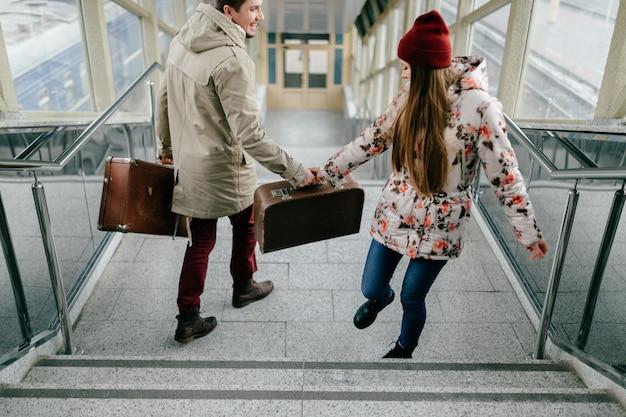 Jóvenes amantes felices llevan maletas marrones vintage en la estación de tren