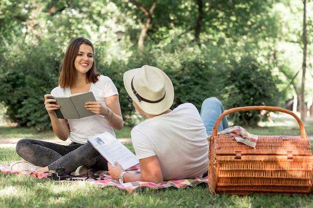 Jóvenes amantes leyendo en el parque