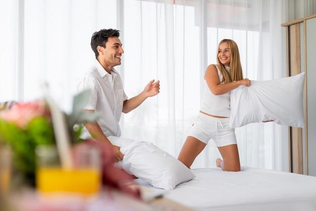 Jóvenes amantes loco luchando almohada en dormitorio en la mañana