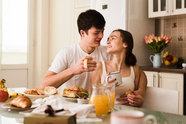 Jóvenes amantes románticos desayunando juntos