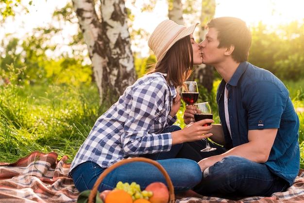 Jóvenes amantes sentados en plaid y besándose