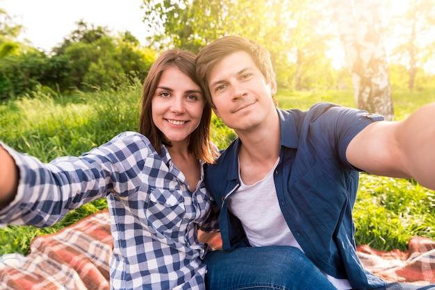 Jóvenes amantes sentados en plaid en bosque y tomando selfie