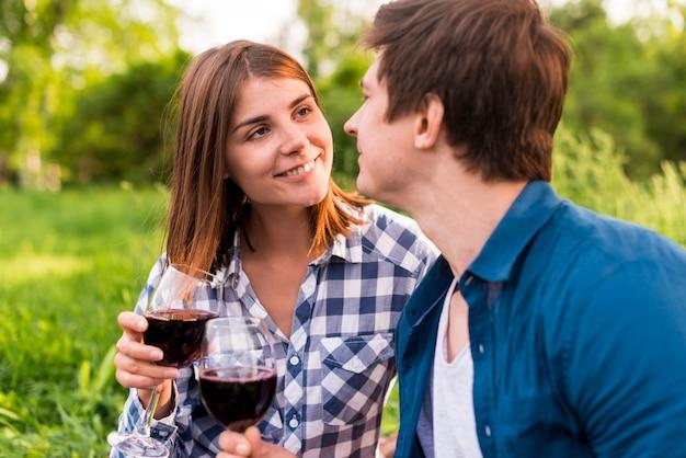 Jóvenes amantes sonrientes tintineando copas de vino afuera