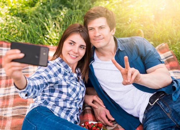 Jóvenes amantes tumbados en manta y tomando selfie
