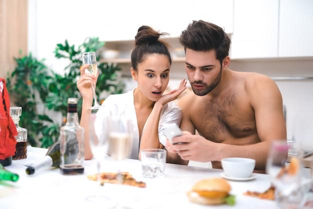 Jóvenes amantes viendo fotos después de una loca fiesta sexual