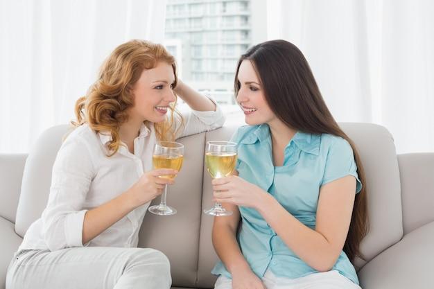 Jóvenes amigas con copas de vino en casa