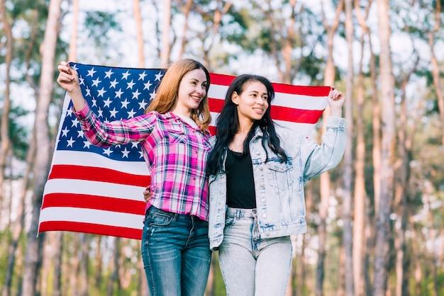 Jóvenes amigas felices abrazando y agitando la bandera de estados unidos