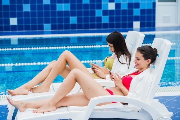 Jóvenes amigas mensajes con un amigo en su teléfono inteligente. concepto de relajación spa y tecnología redes sociales.