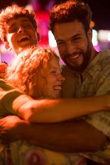 Jóvenes amigos abrazan en el parque de atracciones nocturno