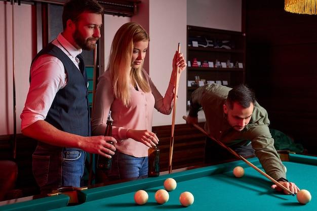 Jóvenes amigos activos están jugando al billar en el bar después del trabajo, tienen tiempo de descanso y ocio, preparándose para lanzar bolas de billar