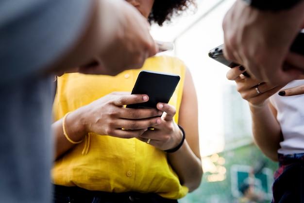 Jóvenes amigos adultos que usan teléfonos inteligentes al aire libre