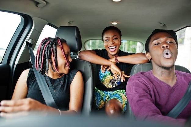 Jóvenes amigos afroamericanos sentados dentro de un automóvil