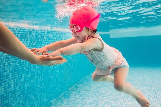 Jóvenes amigos bajo el agua en la piscina