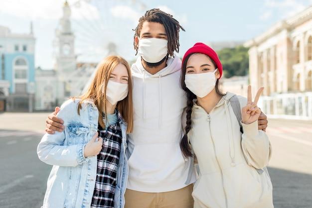 Jóvenes amigos al aire libre con máscara