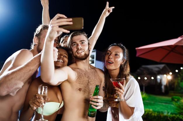 Jóvenes amigos alegres sonriendo, regocijándose, haciendo selfie, descansando en la fiesta