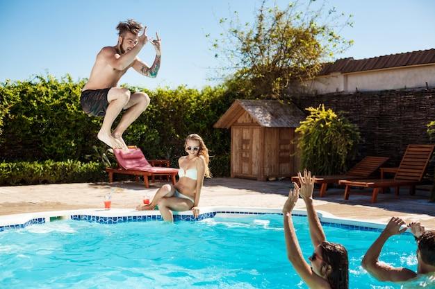 Jóvenes amigos alegres sonriendo, riendo, relajándose, nadando en la piscina