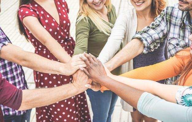 Jóvenes amigos apilando las manos juntas