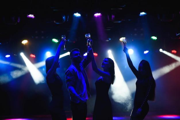 Jóvenes amigos bailando con copas de champagne en las manos.