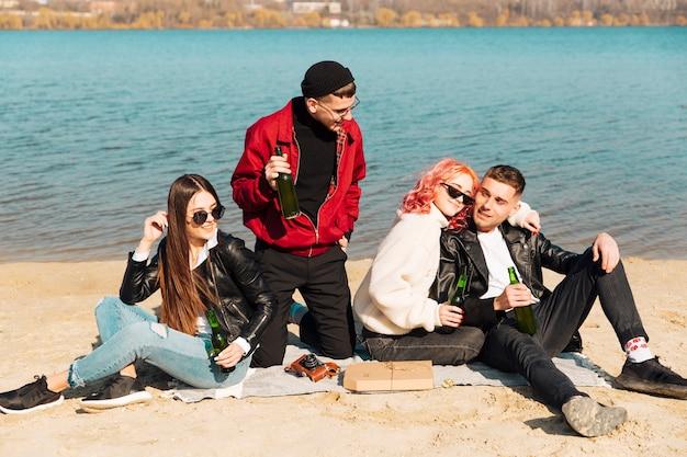 Jóvenes amigos bebiendo cerveza en la soleada playa de primavera