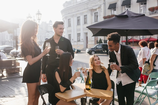 Jóvenes amigos bebiendo champán en una terraza
