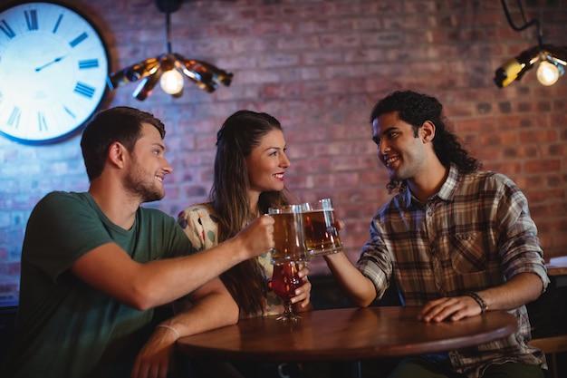 Jóvenes amigos brindando jarras de cerveza