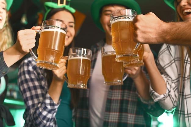 Jóvenes amigos con cerveza celebrando el día de san patricio en el pub