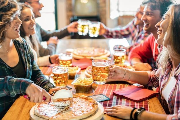 Jóvenes amigos comiendo pizza en casa en reunión de invierno