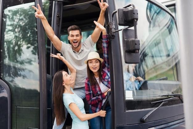 Jóvenes amigos contentos miran fuera del entrenador de viajes.