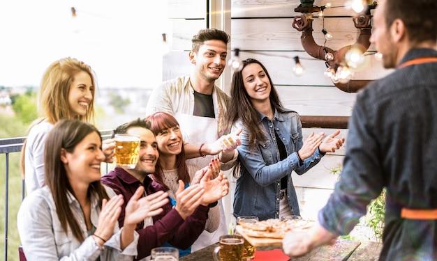 Jóvenes amigos divirtiéndose bebiendo cerveza en el balcón en la cena de la casa