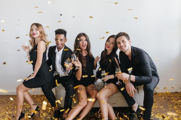 Jóvenes amigos divirtiéndose y bebiendo champán en la fiesta
