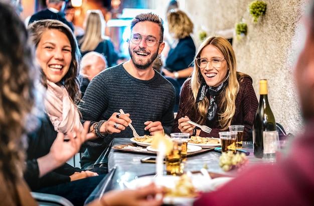 Jóvenes amigos divirtiéndose bebiendo vino blanco en el festival de comida callejera