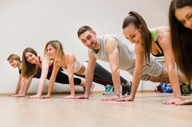 Jóvenes amigos entrenando juntos en el gimnasio
