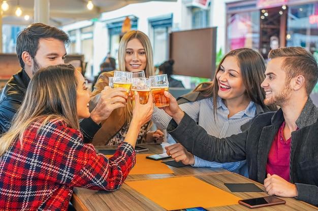 Jóvenes amigos felices bebiendo cerveza