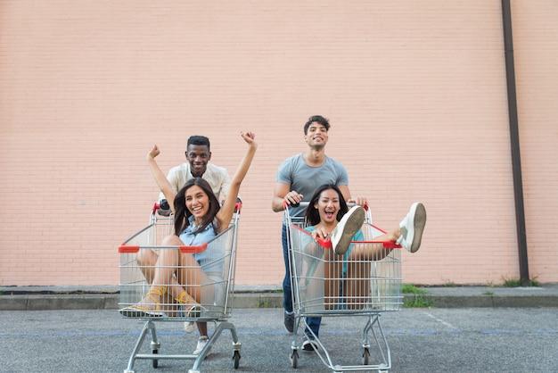 Jóvenes amigos felices corriendo con carritos de compras