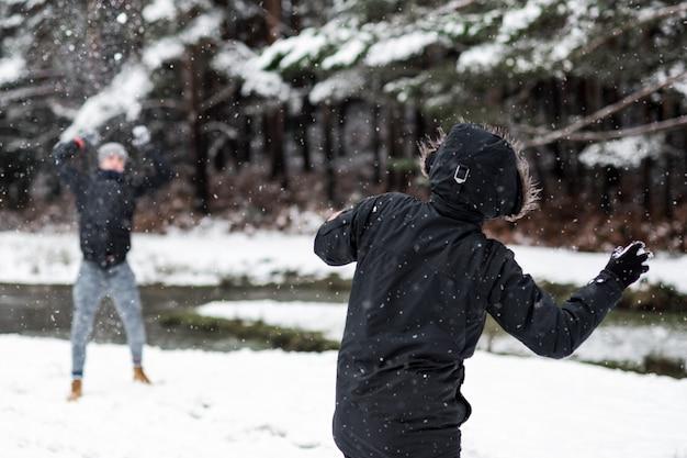 Jóvenes amigos felices disfrutando de lanzar bolas de nieve