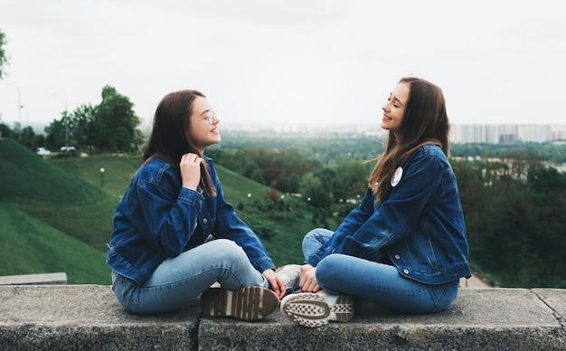 Jóvenes amigos hablando y divirtiéndose en el parque de la ciudad