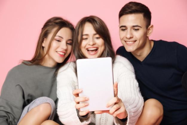 Jóvenes amigos haciendo selfie en tableta en rosa