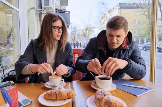 Jóvenes amigos hombres y mujeres estudiantes sentados en un café al aire libre, hablando