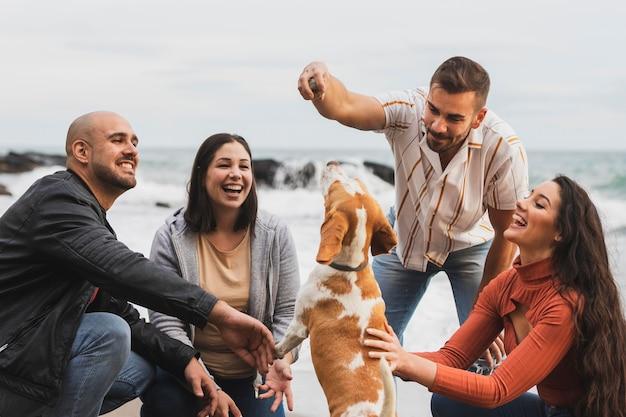 Jóvenes amigos jugando con perro
