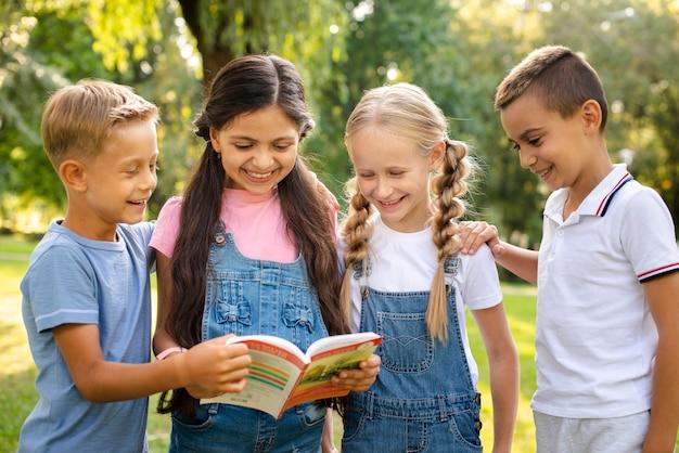 Jóvenes amigos leyendo libro juntos