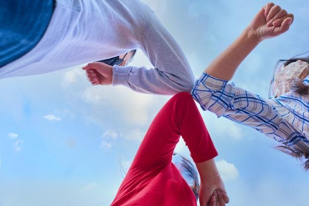 Jóvenes amigos con mascarilla haciendo un nuevo saludo de distanciamiento social con codos para prevenir la propagación del virus corona