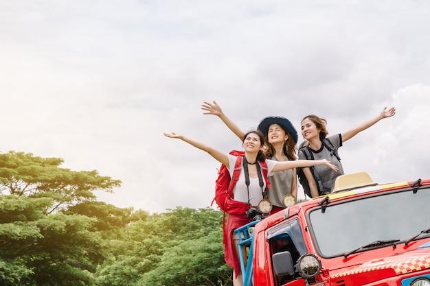 Jóvenes amigos con mochilas en un todoterreno rojo