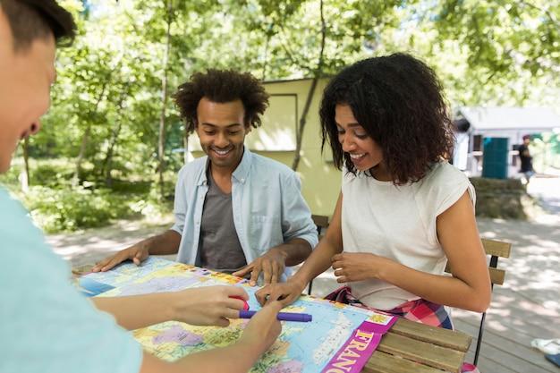 Jóvenes amigos multiétnicos concentrados estudiantes al aire libre estudiando