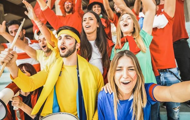 Jóvenes amigos partidarios del fútbol animando y viendo el partido de la copa de fútbol en el estadio internacional