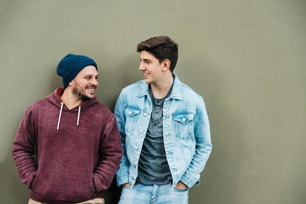 Jóvenes amigos de pie cerca de la pared gris