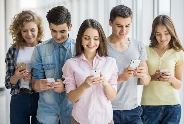 Jóvenes amigos positivos que usan sus teléfonos.