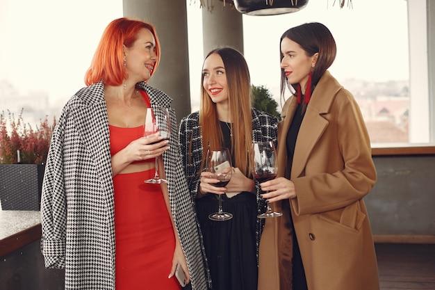 Jóvenes amigos riendo bebiendo vino rosado de cristal fuera
