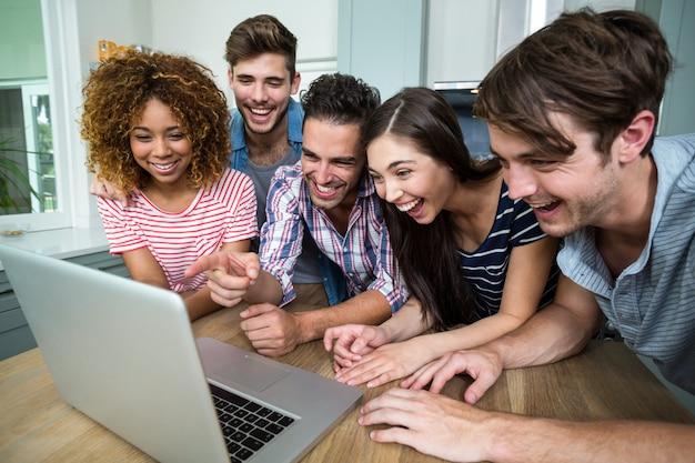 Jóvenes amigos riéndose mientras mira en la computadora portátil sobre la mesa