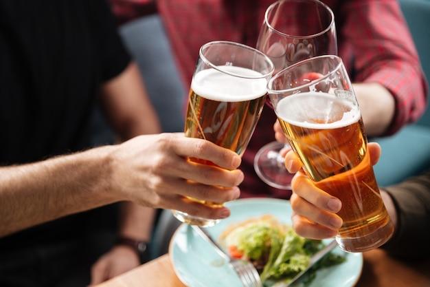 Jóvenes amigos sentados en la cafetería mientras bebe alcohol.