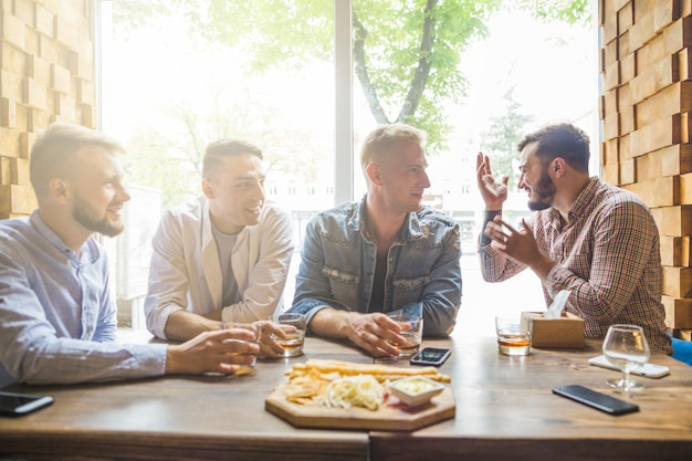 Jóvenes amigos sentados en el restaurante disfrutando de las bebidas
